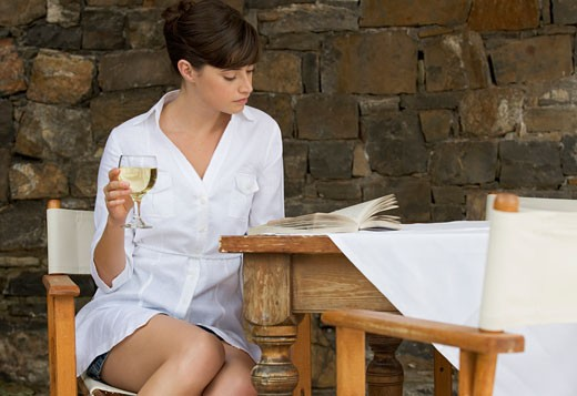 A woman drinking a glass of wine sitting at a table : Stock Photo