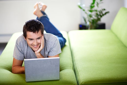 Young man with a laptop, laying on a bed : Stock Photo