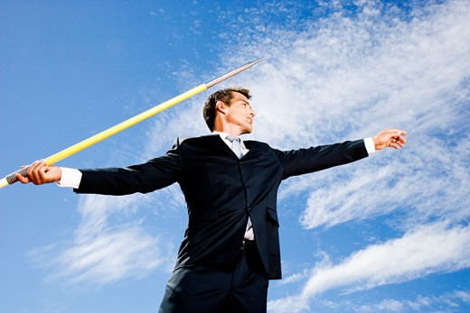 Stock Photo: 1804R-12889 Portrait of a businessman throwing a javelin
