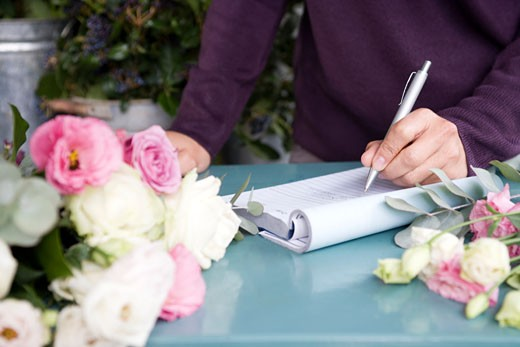 Woman florist taking an order over the telephone : Stock Photo