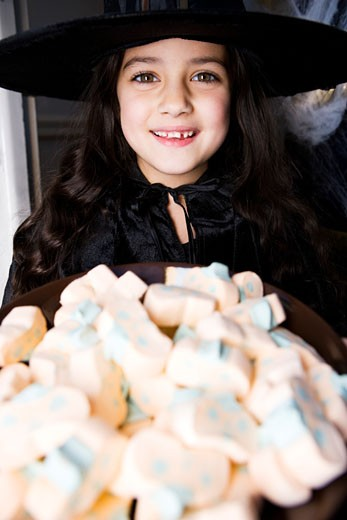 Girl in a witch's costume at a Hallowe'en party, holding a tray of sweets : Stock Photo