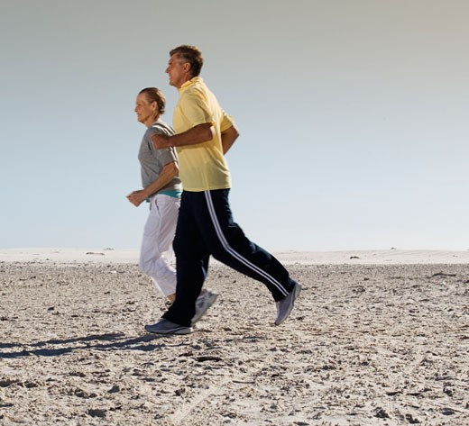 A mature couple jogging on a beach : Stock Photo