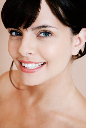 Portrait of young woman with dark hair in a bun, smiling : Stock Photo