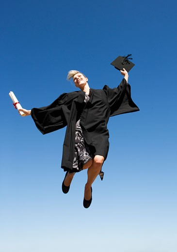 A graduate jumping for joy : Stock Photo