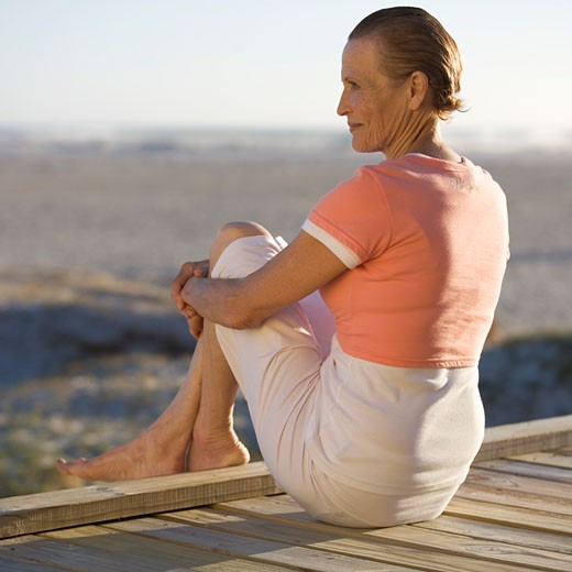 Stock Photo: 1804R-13673 A mature woman sitting on a boardwalk