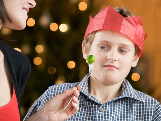 A boy refusing to eat a Brussels sprout : Stock Photo