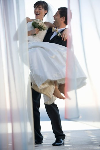 A groom carrying his bride : Stock Photo
