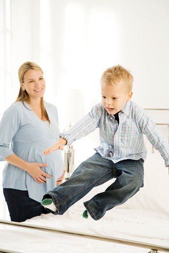 A mother and her young son making the bed : Stock Photo