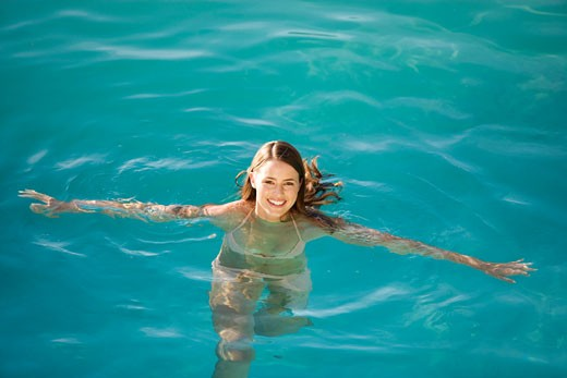 A young woman swimming in a pool : Stock Photo