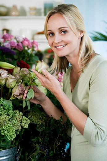 Woman choosing flowers in a florist's shop : Stock Photo