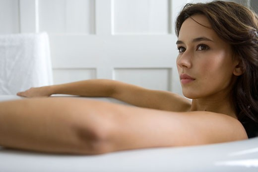 Stock Photo: 1804R-14692 A young woman laying in a bath