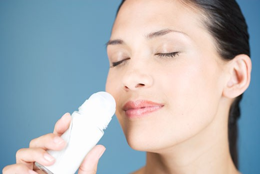 A young woman smelling a de-odorant roll-on : Stock Photo