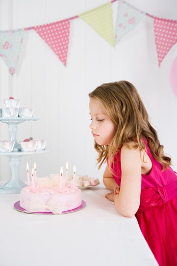 little girl looking at birthday cake : Stock Photo
