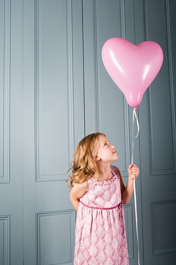 Stock Photo: 1804R-15145 little girl in party dress looking at her pink heart shaped balloon