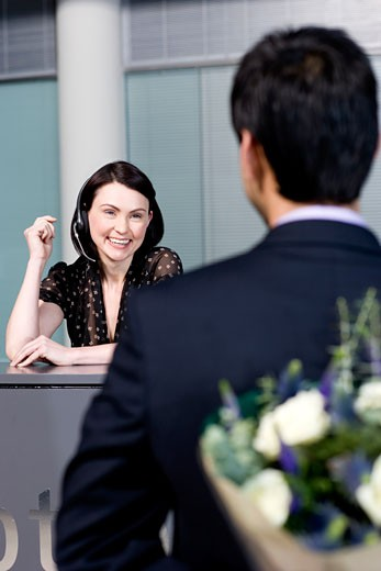 Businessman with bouquet of flowers being greeted by office receptionist : Stock Photo
