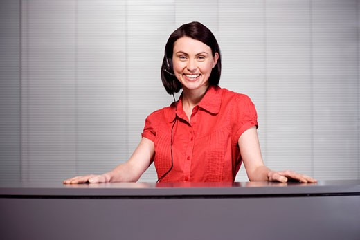 Office receptionist in a red blouse, smiling : Stock Photo
