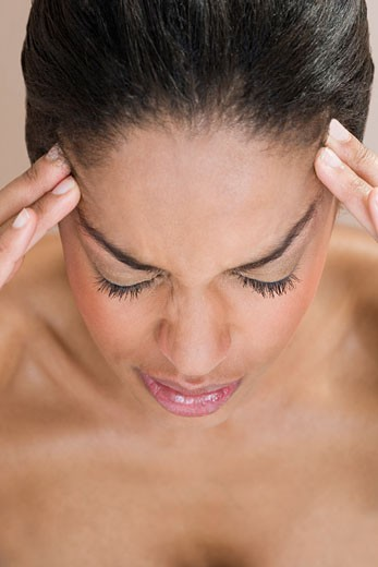 A woman with a migraine, fingers pressed to forehead : Stock Photo