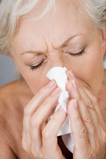 Stock Photo: 1804R-16049 A senior woman blowing her nose