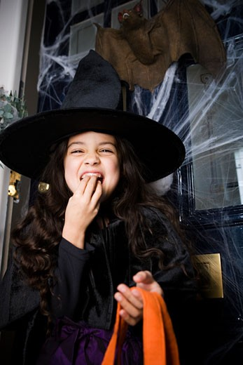 Girl in a witch's costume at a Hallowe'en party, eating sweets  : Stock Photo