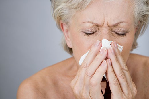 A senior woman blowing her nose : Stock Photo