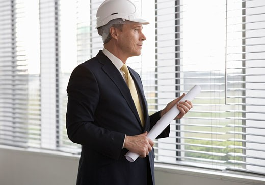 An architect wearing a hard hat holding plans : Stock Photo