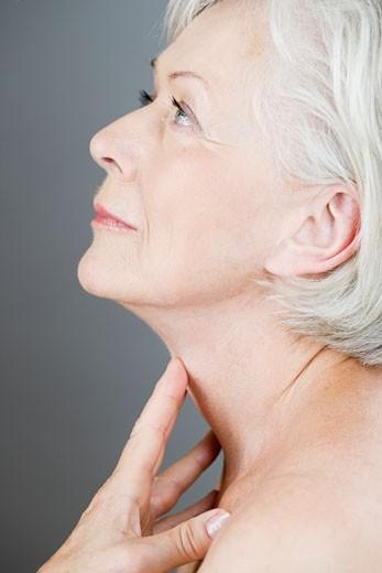 A senior woman touching her neck : Stock Photo