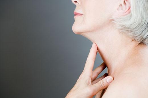 Stock Photo: 1804R-16197 A senior woman touching her neck