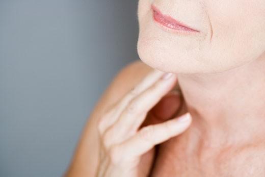 Stock Photo: 1804R-16201 A senior woman touching her neck
