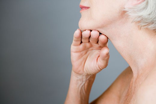 A senior woman touching the skin under her chin : Stock Photo