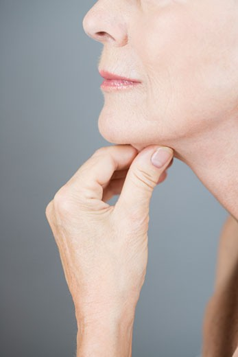 Stock Photo: 1804R-16213 A senior woman pinching the skin under her chin