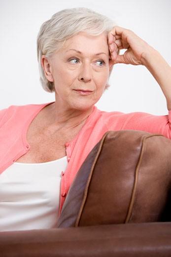 A senior woman sitting on a sofa : Stock Photo