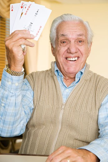 An elderly man playing cards : Stock Photo