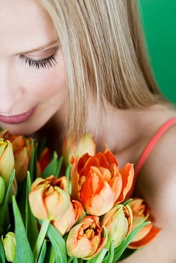 Stock Photo: 1804R-17041 A young woman holding a bunch of orange tulips, looking down