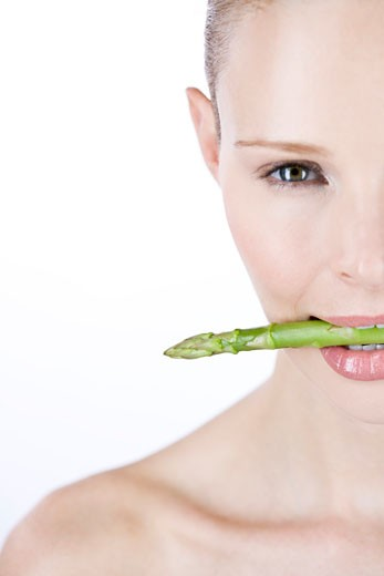 A young woman with a piece of asparagus in between her teeth, right side : Stock Photo