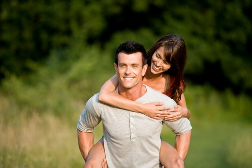 A man giving his girlfriend a piggyback : Stock Photo
