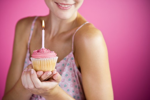 Stock Photo: 1804R-17365 A Young Woman Holding A Birthday Cake With A Candle