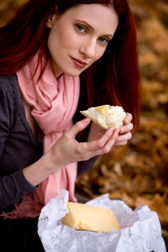 A young woman eating some bread and cheese : Stock Photo