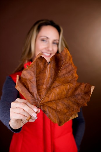 Stock Photo: 1804R-17858 A mid adult woman holding a dried leaf, smiling