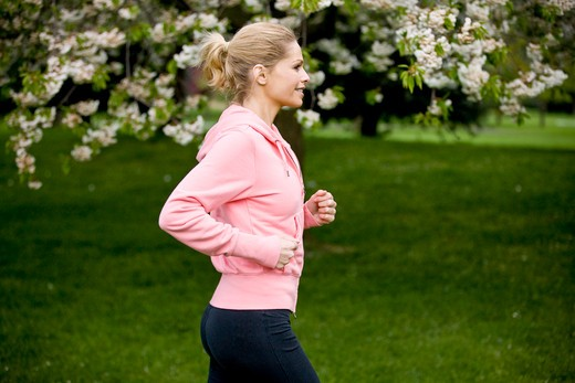 Stock Photo: 1804R-18023 A mid adult woman jogging in the park, in springtime