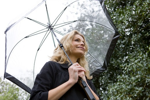 Stock Photo: 1804R-18130 A mid adult woman holding an umbrella