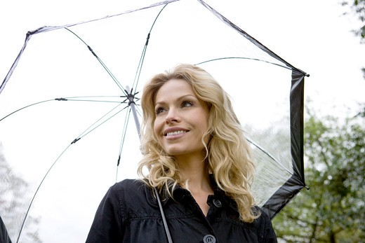 A mid adult woman holding an umbrella : Stock Photo