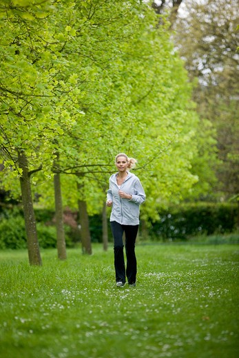 A mid adult woman jogging in the park : Stock Photo
