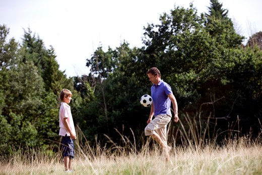 A father and son playing football : Stock Photo