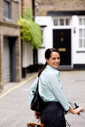 Stock Photo: 1804R-18891 A businesswoman standing on her bicycle, smiling