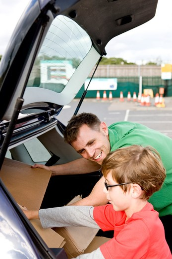 A son helping his father recycle cardboard boxes : Stock Photo