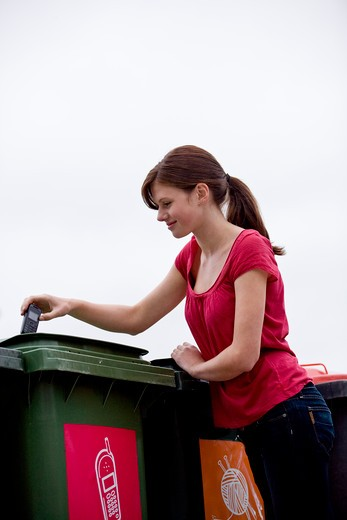 A teenage girl recycling a mobile phone : Stock Photo