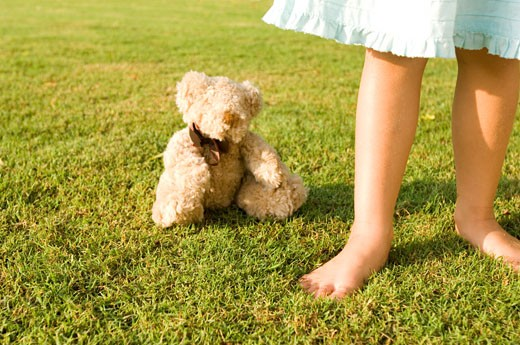A young girl standing by a teddy bear : Stock Photo