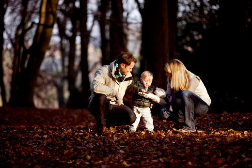 A child looking at a leaf with his parents in the park : Stock Photo