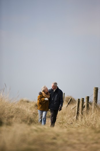 A senior couple walking along a path together : Stock Photo