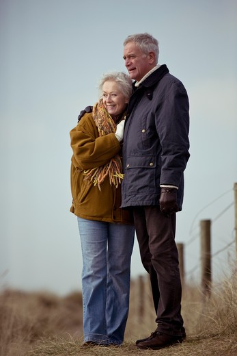 A senior couple standing, embracing : Stock Photo
